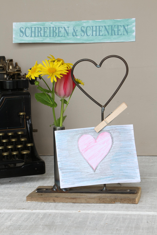 Vase mit Herz auf altem Holz mit Wäscheklammer
